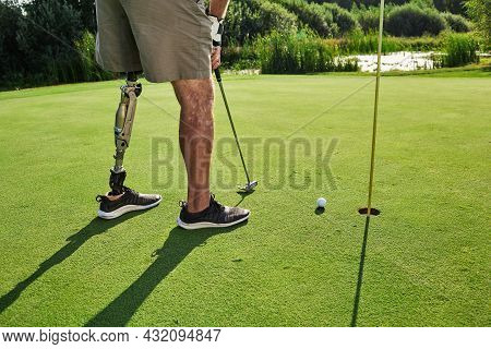Professional Golfer With Prosthetic Leg Hitting With Putter On Golf Ball During Golfing At Sunny Day