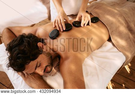 Handsome Man At Spa Resort Receives Hot Stone Massage. Hot Stone Massage Therapy Using Smooth, Flat,