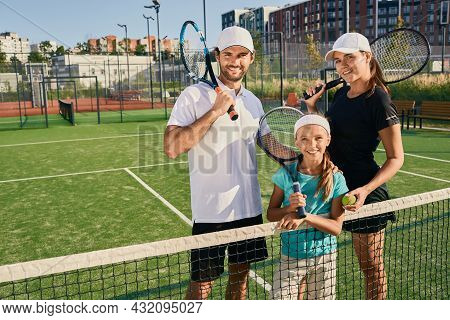 Family Of Tennis Players Standing On Tennis Court Outdoor With Rackets. Sporty Family Playing Tennis