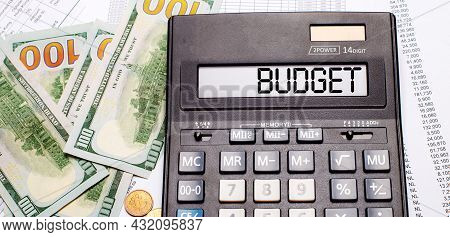 Against The Background Of Cash And Documents Is A Black Calculator With The Text Budget On The Score