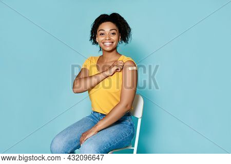 Young Black Woman With Plaster Band Aid After Covid Vaccine Shot Smiling On Blue Studio Background