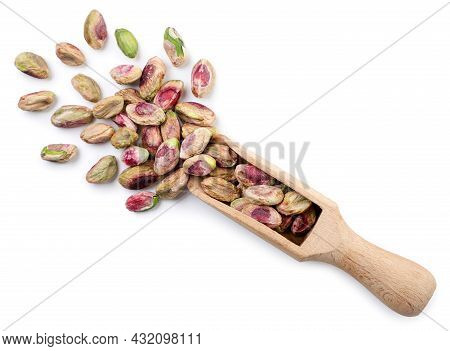 Peeled Pistachios In A Wooden Scoop Close Up On A White Background, Isolated. Top View