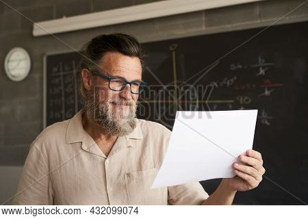 Close-up Of The Face Of A Smiling College Professor. He Is Holding Some Documents, An Exam, A Paper.
