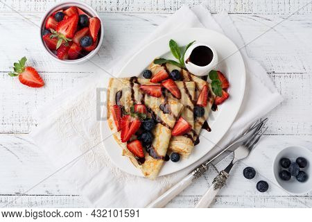 Homemade Crepes Pancakes With Chocolate Sauce , Fresh Strawberry And Honey For Breakfast In Beautifu