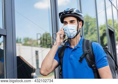 Arabian Deliveryman In Bike Helmet And Medical Mask Talking On Smartphone On Urban Street