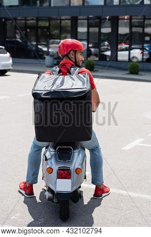 Side View Of Smiling Muslim Deliveryman With Thermo Backpack Sitting On Scooter On Urban Street