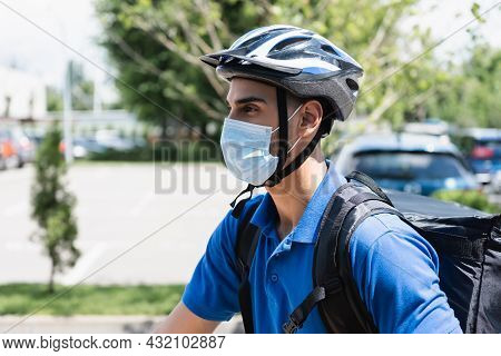 Muslim Deliveryman In Safety Helmet And Medical Mask Outdoors