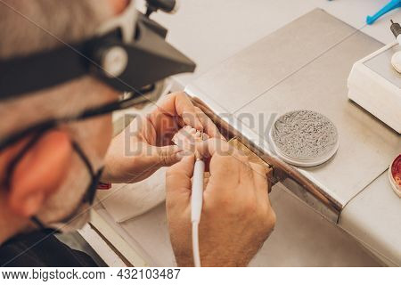 Close-up View Of The Hands Of An Adult Man Modelling A Dental Mould With Wax Using An Electric File