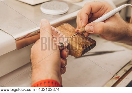 Close-up View Of The Hands Of A Professional Using A Tip Of A Sharpener To Apply Wax To A Dental Mou