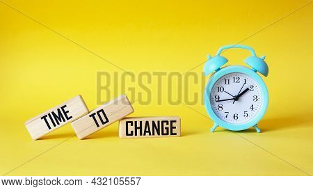 Time To Chance, The Text Is Written On Wooden Blocks And A Yellow Background With A Clock. A Promisi