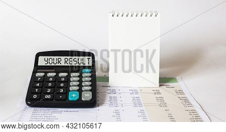 The Word Your Result, Written On The Calculator Display Lying On The Documents With Calculations And