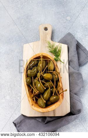 Canned Capers In Wooden Dish, Tapenade And Bread On Trendy Concrete Background. Top View
