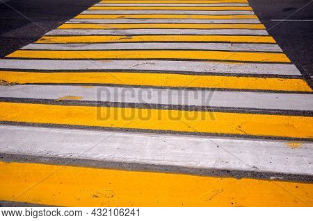 Road Marking Pedestrian Crossing On Cracked Asphalt, Abstract Background. White And Yellow Pedestria