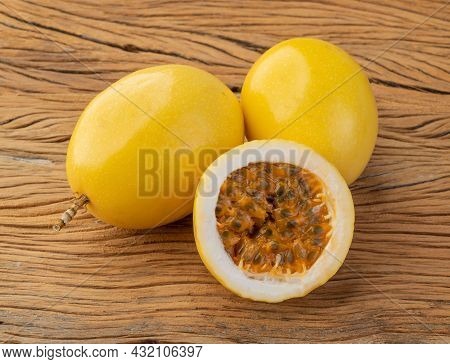 Passion Fruits With Cut Fruit Over Wooden Table.