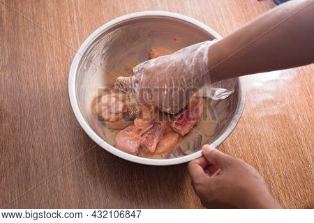 Hand Marinating Fresh Uncooked Chicken In A Steel Bowl. Male Preparing Raw Chicken To Deep Fry At Ho