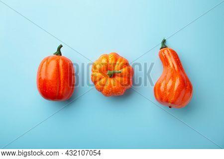 Creative Autumn Composition. Orange Pumpkins On Blue Background. Top View
