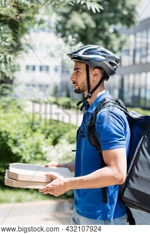 Side View Of Young Muslim Deliveryman In Helmet Holding Pizza Boxes On Urban Street