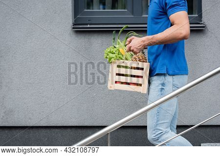 Cropped View Of Deliveryman Holding Box With Fresh Vegetables Near Building