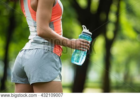Partial View Of Fit Woman In Shorts Holding Sports Bottle While Standing In Park