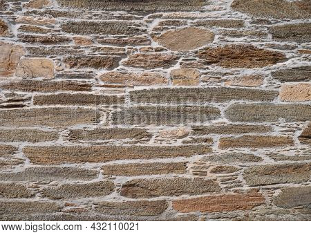 Ancient Natural Brown Stone Wall With Gray Cement Background. Irregular Masonry