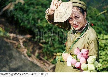 Beautiful Young Vietnamese Woman In Traditional Ao Dai Dress And Headwear Using Woodwn Fan To Hide F