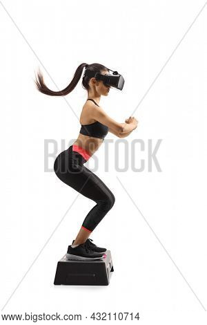 Full length profile shot of a young woman exercising on a step aerobic platform with a vr headset isolated on white background