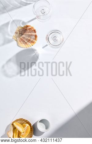 Empty table mock up in contemporary style on light background. White restaurant table with shadow glass in summer style. Harsh lights glass on white table and copy space