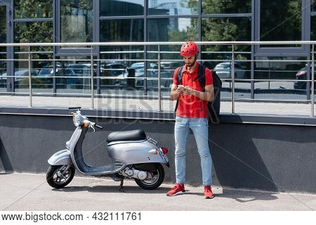 Young Arabian Deliveryman With Thermo Backpack Using Smartphone Near Scooter And Building Outdoors