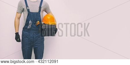 The worker in professional uniform with toolbox in hand on the gray background