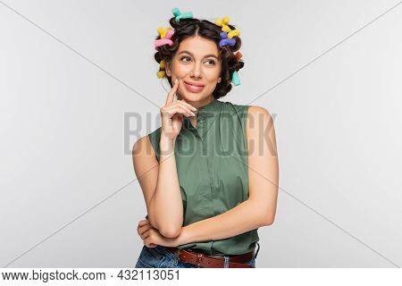 Dreamy Young Woman With Colorful Hair Curlers Smiling Isolated On Grey