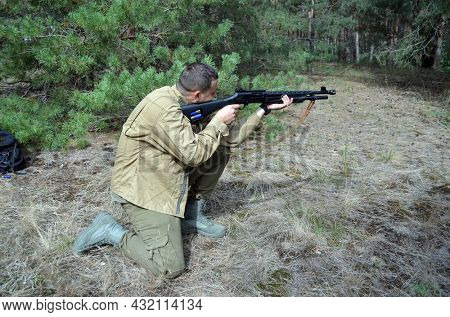 Man with Turkish 12-gauge rifle Hatsan Escort MP(pump action shotgun). Unformal shooting range near Kiev. September 6,2021. Kiev Region, Ukraine