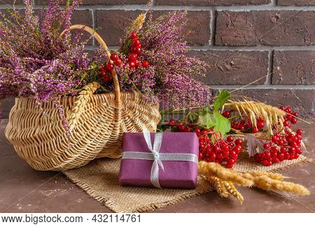 Autumn Composition Of Heather In A Wicker Basket, Viburnum, Wheat Ears And Gifts, Still Life