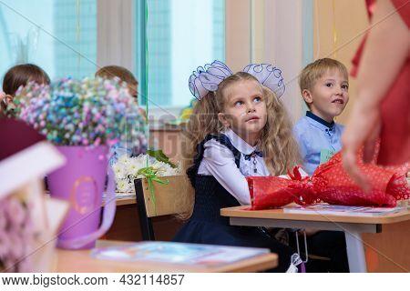 On September 1, Children Sit At Their Desks In Class. First Graders Listen Carefully To The Teacher