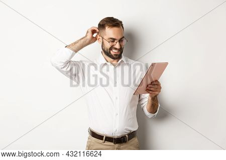 Confused Male Manager Looking Puzzled At Digital Tablet, Scratching Head Doubtful, Standing Over Whi