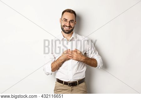 Touched And Thankful Business Man Holding Hands On Heart, Smiling Grateful, Standing Against White B