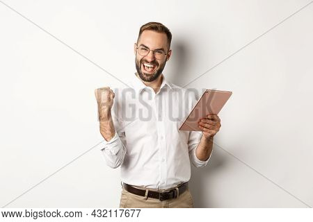 Successful Businessman Rejoicing On Winning Online, Reading On Digital Tablet And Making Fist Pump,
