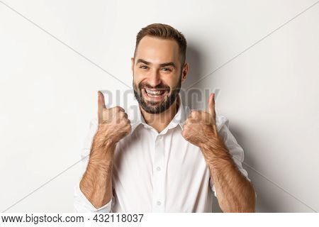Close-up Of Satisfied Bearded Guy In White Shirt, Showing Thumbs Up In Approval, Like And Agree, Pos