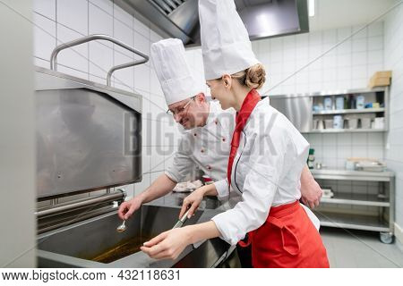 Chefs in large commercial kitchen cooking meals together