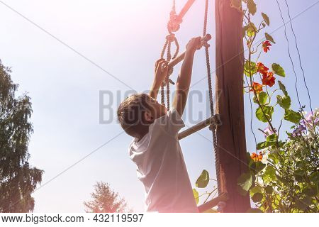 Cute Athletic Little Boy Child Climbing On Rope Ladder High Up. Amusement Park For Kids. Outdoor Act