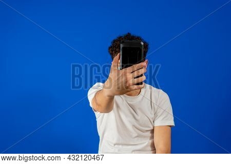 Image Of Positive Youngster Guy With Curly Hair Wearing Casual Clothing And Backpack Holding Smartph