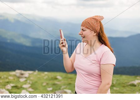 Young Female Traveler Use Phone In The Mountains. Connectivity Mobility Technology. Travel Lifestyle