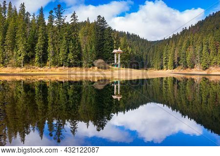 Mountain Lake Among Coniferous Forest. Beautiful Autumn Landscape With Fluffy Clouds On The Sky. Sce