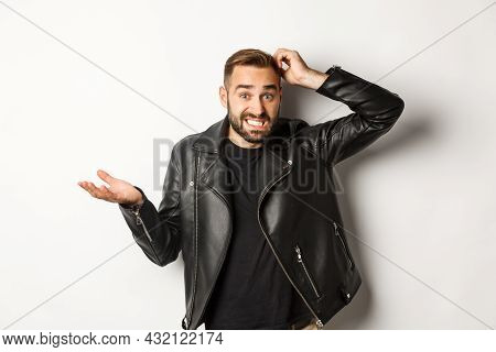 Confused Bearded Guy In Cool Leather Jacket Shrugging, Scratch Head Puzzled And Clueless, Standing O