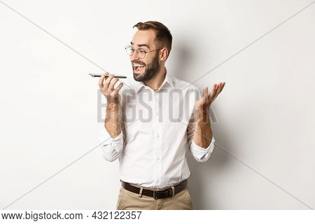 Excited Businessman Talking On Speakerphone And Smiling, Record Voice Message With Ecstatic Face, St