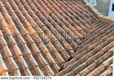 Close Up Of A Rooftop Seen From Above. Old Roof Tiles, Some Of Them With Moss. Evora, Portugal. Euro