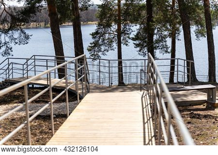 A Fragment Of A Wooden Staircase With A Metal Fence In A Pine Forest On A Sunny Summer Day. Descent