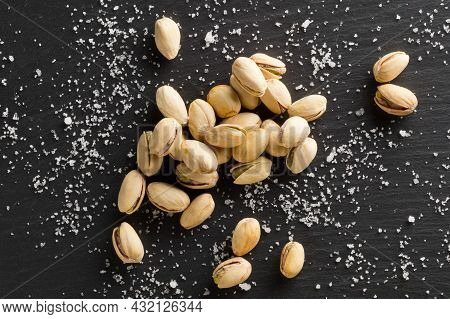 Heap Of Salted, Roasted Green Pistachio Nuts Snack On Black Background With Sea Salt, Healthy Food S