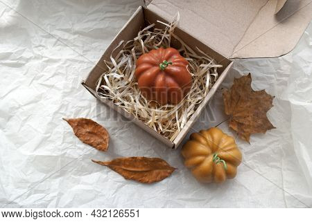 Candlemaking. A Pumpkin-shaped Beeswax Candle Is In Craft Packaging. Autumn Mood, A Gift For The Day