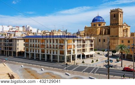 Elche, Spain - July 26, 2021: A birds-eye-view over the Palau Square in Elche, Spain, highlighting the dome and the belltower of the Basilica of Santa Maria church, dedicated to the Virgin Mary