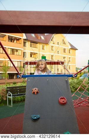 Caucasian Girl Climb The Climbing Wall In The Playground